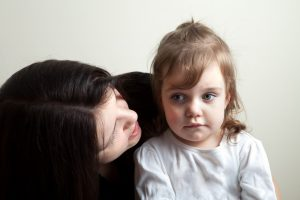toddler age girl getting spoken to by her mother