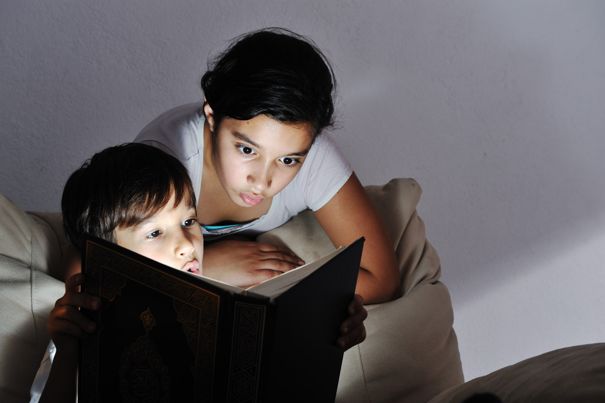 brother and sister reading light book at night