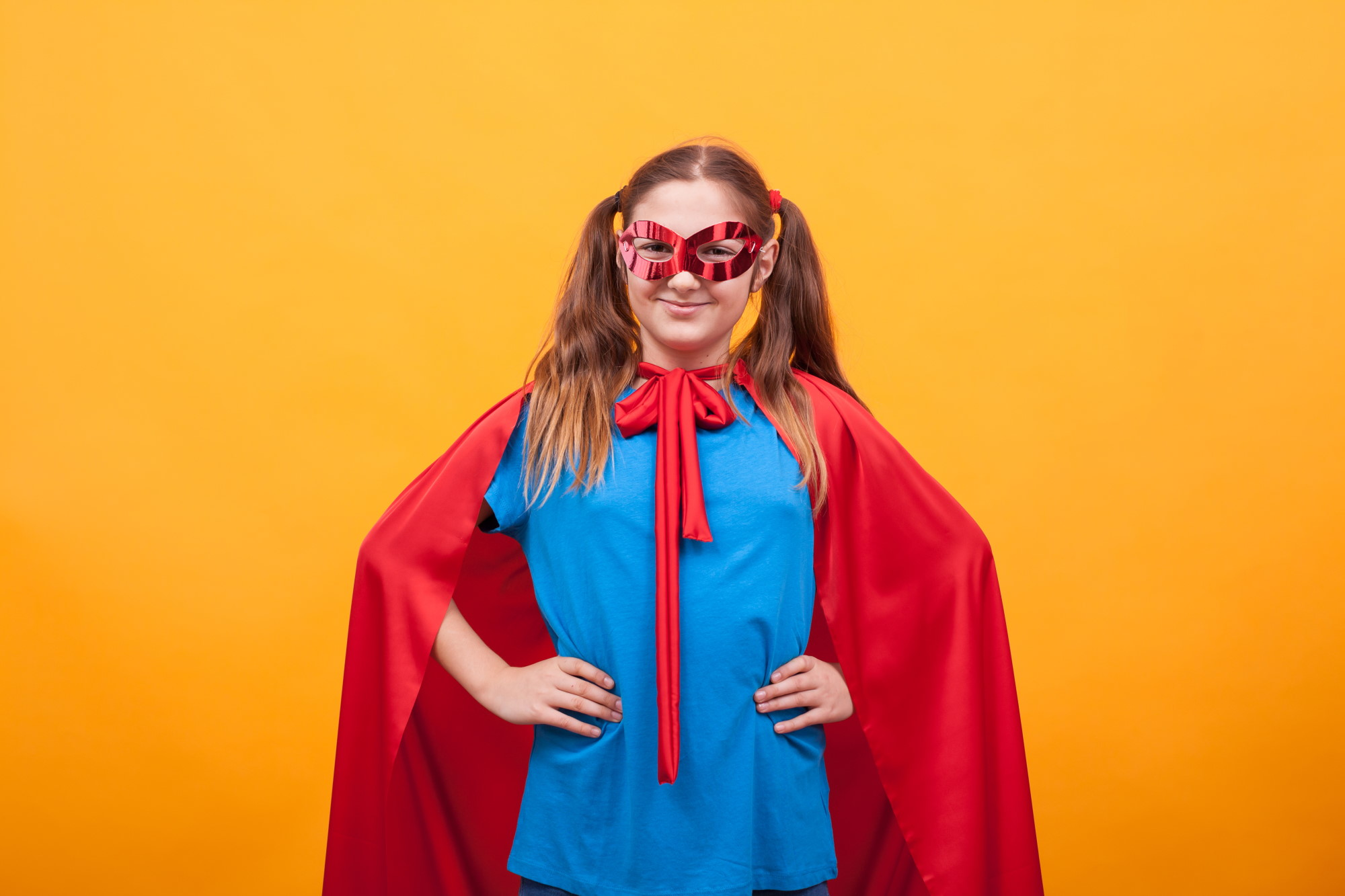 little girl in super hero costume ready to save the world from bad guys over yellow background